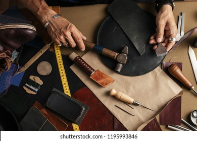 Top view of male shoemaker hands holding cobbler tools for making new shoes at his workshop over his working place background