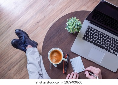 top view of man in casual wear sitting at coffee table with laptop, cup of coffee and writing somethings on mini notbook