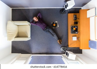 Top view of a man chilling out on the floor listening to music