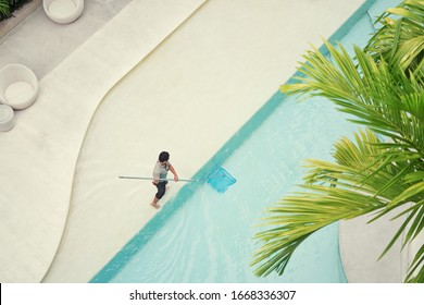 Top view of man cleaning swimming pool.