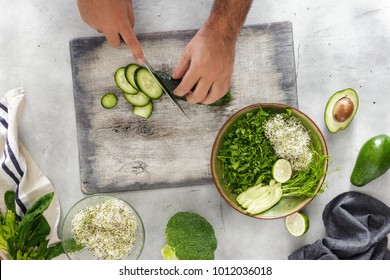 Top view man cooking a detox salad on a white background
