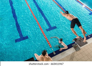 Top view of a man diving from a starting block into a swimming pool