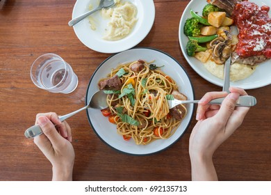 top view of a man enjoying a delicious meal on the wood table, pork chili pasta