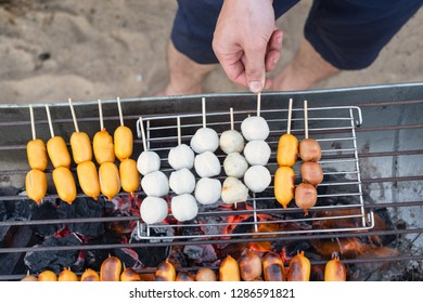 Top view of man grilling sausage, meatball and fishball on stove. BBQ party style.