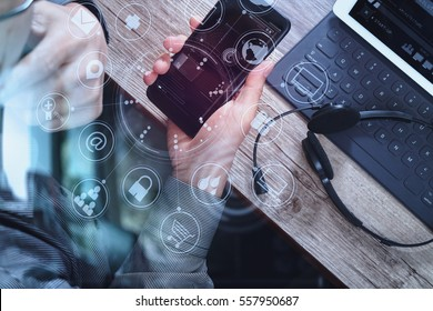 top view of man hand using VOIP headset with digital tablet computer docking keyboard,smart phone, it support, call center and customer service help desk on wooden table,virtual interface icons screen