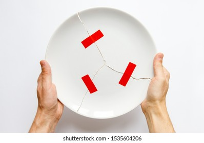 Top view of man hands holding a broken white plate, parts glued with red tape. Metaphor for divorce, relationships, friendships, crack in marriage. Love is gone. Isolated on white background.