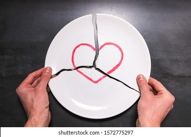 Top view of man hands holding a broken white plate with heart symbol. Metaphor for divorce, relationships, friendships, crack in marriage. Love is gone
