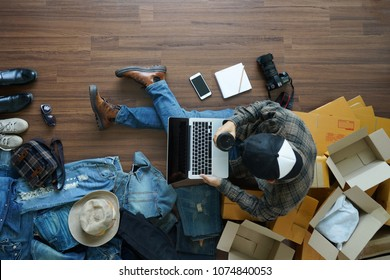 Top view of man holding coffee cup working laptop computer with fashion accessories on wooden floor from home. With postal parcel, Selling online ideas concept design