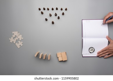 Top view of a man organizing strategy while writing down ideas in blank notebook with puzzle pieces, chess and compass on gray table.