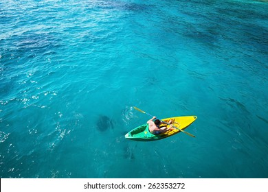 top view of man paddling on kayak in turquoise water