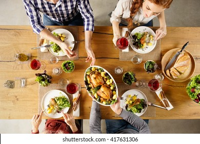 Top view of man passing food bowl to friend. High angle view of happy young friends eating together at home. Happy men and women having lunch with roasted chicken.