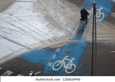 Top view of man rides bicycle in partly snow covered bike-lane in mid-winter, Copenhagen, Denmark.
