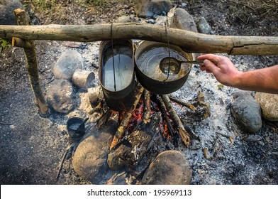 top view of man stirs ladle water that is prepared in a hike in the cauldrons, hanging over the fire