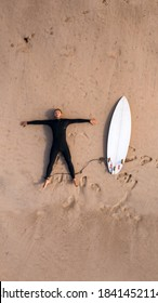 Top view of a man surfer in wetsuit with a surfboard lying on the sand on the beach. Tired after surfing. Having a rest