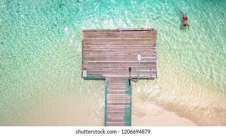 Top view of man swimming in the sea near jetty in Maldives