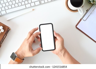 Top view of man using mobile phone in office. Blank screen for display montage