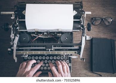 top view of man using vintage manual typewriter on rustic wooden table