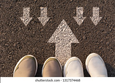 Top view of man wearing white shoes choosing a way marked with white arrows. Chooses the right path concept.