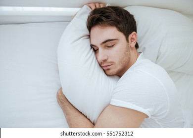 Top view of man in white shirt sleeping on bed