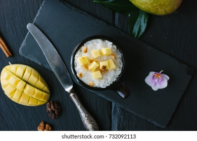 Top view of mango and rice dessert over black background.