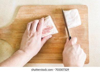 The top view of a man's hand cuts a piece of raw pork fat on wooden board