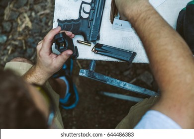 Top view of man's hands refilling black handgun