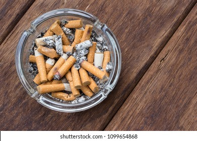 Top view of many cigarette stubs and ash in a glass ashtray on wooden table