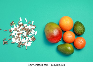 Top view of many medicine white pills and brown capsule, and many fresh exotic fruits isolated on green background with copy space.Choice between medicine pills and natural fresh fruits.