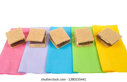 top view of many s'mores lined up in a row on colorful napkins, ready for campfire party. Popular treat for Girl Scouts.