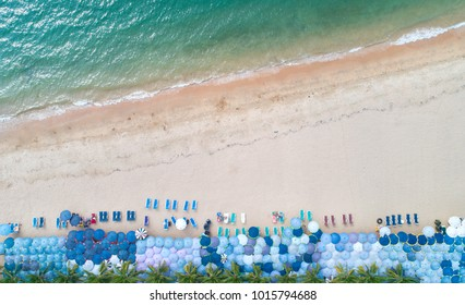 top view of many of umbrellas and beach chairs on the beach with tropical clear sea water on the top at Koh Larn island, Pattaya, Thailand