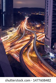 top view of a massive highway intersection  passing trough the skyscraper in the metropolitan area of Kuala Lumpur in Malaysia. Night view with car light trace enlightening the curvy road.