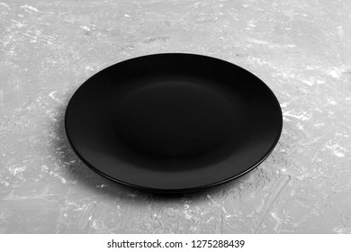 Top view of matte round empty black plate on dark cement background copy space for you design. Perspective view.
