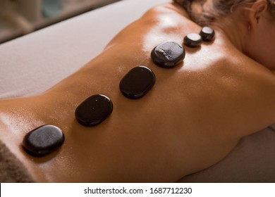 Top view of mature woman relaxing during hot stone massage