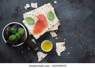 Top view of matzoh, salmon and dates over grey stone background, horizontal shot with copy space