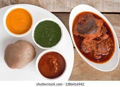 Top view of a meal of Nigerian Amala, Ewedu and Gbegiri Soup Served with Goat Meat Stew in a white bowl and white tray on a wooden table
