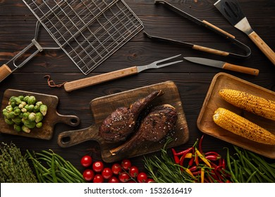 top view of meat, corn, chili peppers, cherry tomatoes, green peas, greenery, brussels sprouts on cutting board and grill tools