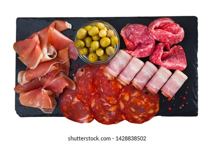 Top view of meat platter - sliced dry-cured jamon, bacon, chorizo and salami on slate serving board with olives. Isolated over white background