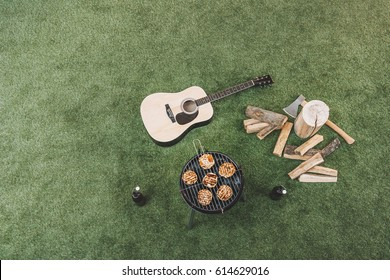 Top view of meat preparing on grill, beer bottles and guitar on grass
