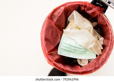 Top view medical gloves, dispose mask and infectious waste in red plastic bag infection bin.