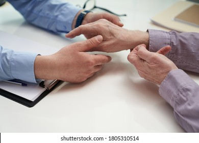 Top view of medical worker hands performing a rheumatological hand examination on an elderly patient
