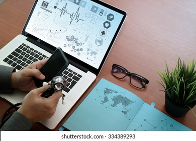 top view of Medicine doctor hand working with modern computer and smart phone with social media network on wooden desk as medical concept