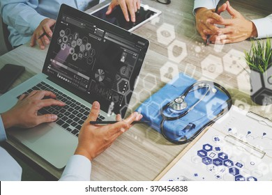 top view of Medicine doctor hand working with modern computer and digital pro tablet with his team with graphics medical diagram on wooden desk