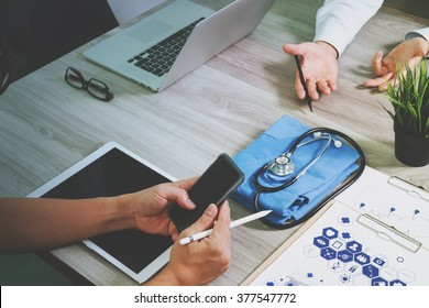 top view of Medicine doctor hand working with modern computer and digital tablet and smart phone with blank screen with his team on wooden desk as medical concept