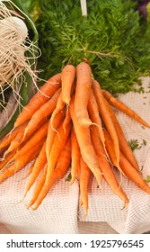 top view, medium distance of a bunch of freshly picked, local, raw French carrots, with greens attached, on display and for sale at a tropical farmers market