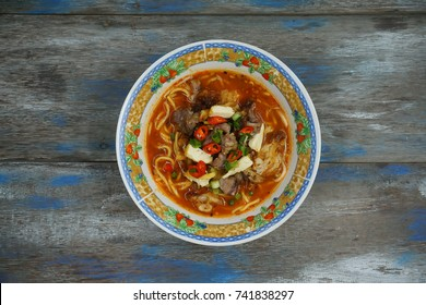 Top view of Mee Kuah, a traditional noodle soup isolated on wooden rustic table