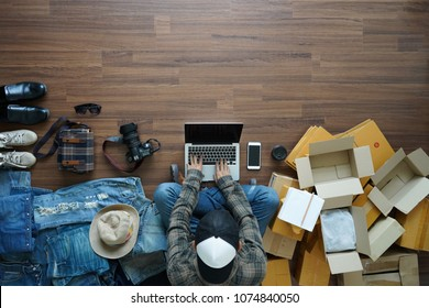 Top view of men working laptop computer with fashion accessories on wooden floor from home. With postal parcel, Selling online ideas concept