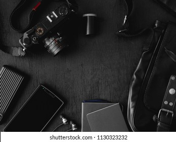Top view of Men's accessories concept with retro camera, smartphone, powerbank, leather bag and glasses on black table background.
