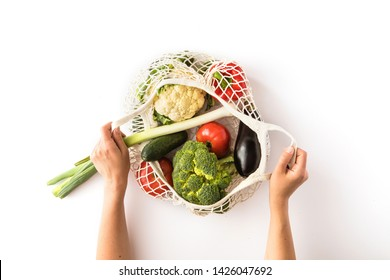Top view of mesh shopping bag with organic eco vegetables isolated on white background. Caring for the environment and the rejection of plastic concept