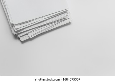 Top view of messy arrangement of pile of white office blank paper on white background. Photo with copy blank space.