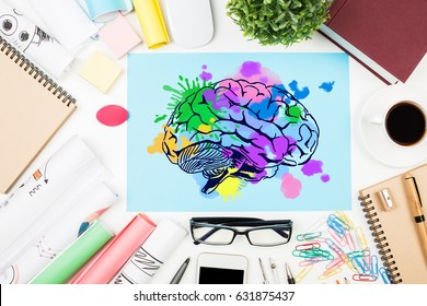 Top view of messy office desktop with coffee cup, supplies and colorful brain sketch. Creative mind concept